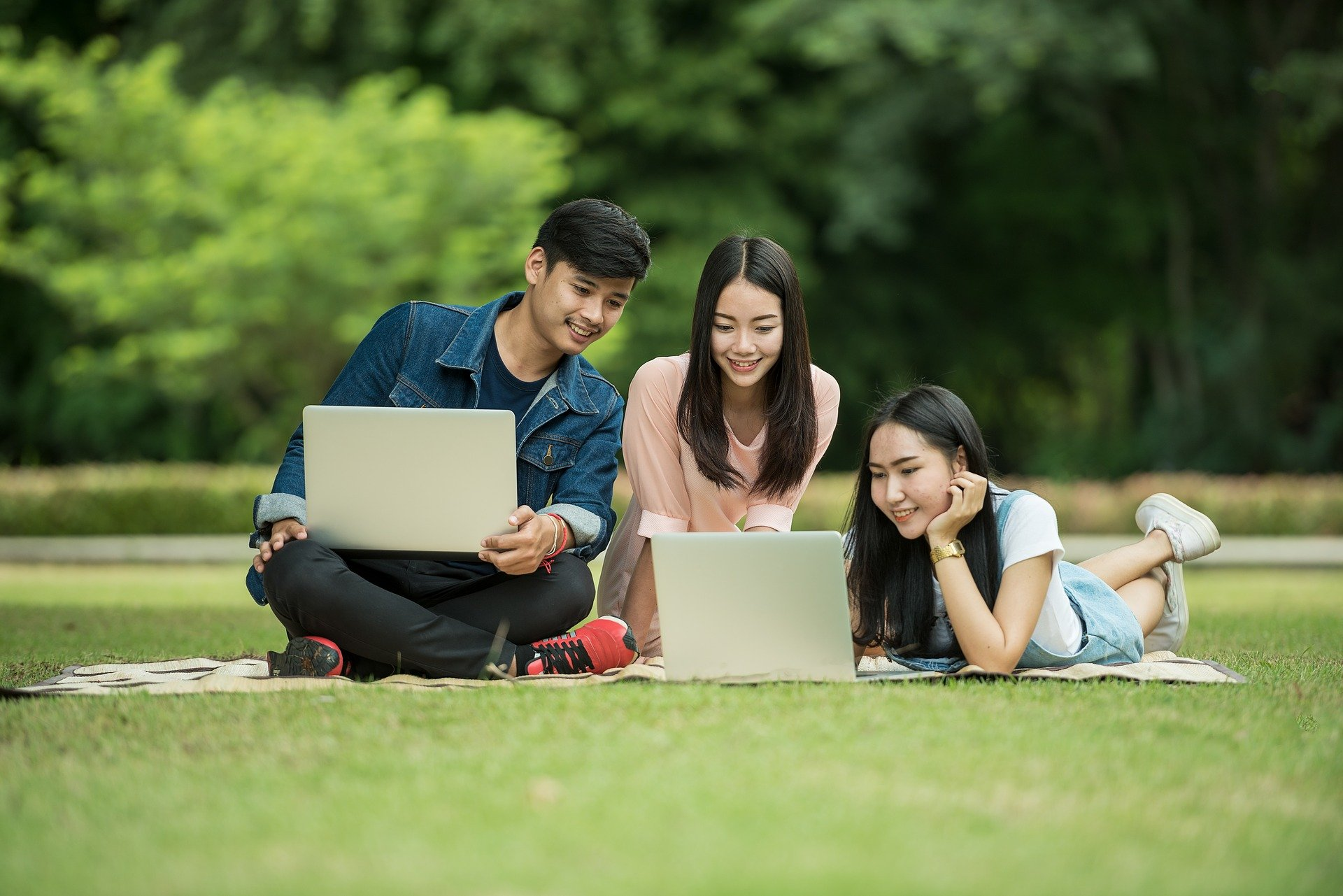 Three students studying together outside on their laptops